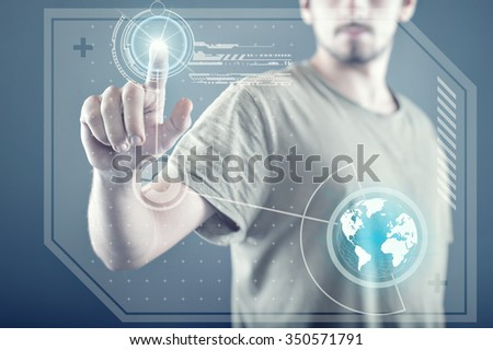 Young man standing and working wth touch screen technology - stock photo