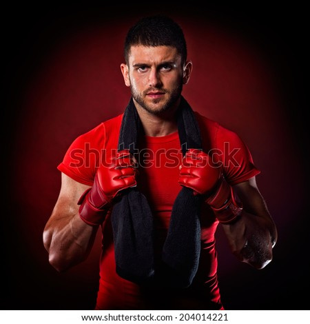 young man standing by bag boxing in studio - stock photo