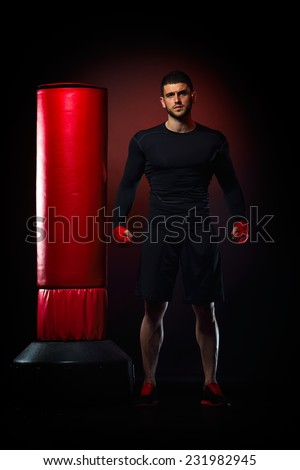 young man standing by boxing bag in studio - stock photo