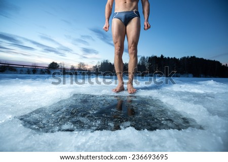 Young man standing by ice hole and ready to swim in the winter water - stock photo