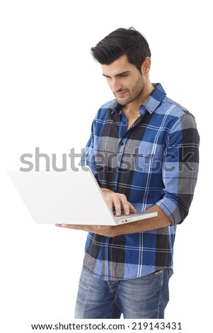 Young man standing, holding laptop computer, working. - stock photo