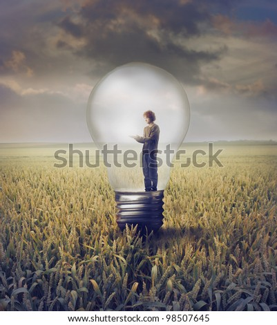 Young man standing in a light bulb on a wheat field - stock photo
