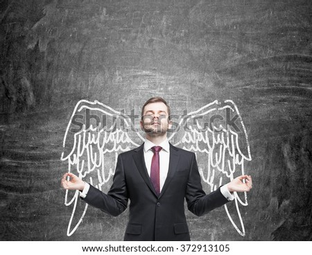 young man standing in a posture of meditation in front of a blackboard with angel wings painted on it as if they were his. Front view. Concept of lending wings. - stock photo