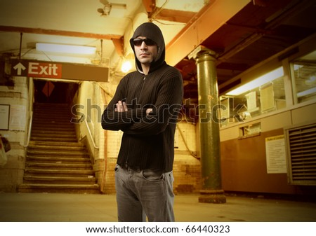 Young man standing in an underground station - stock photo
