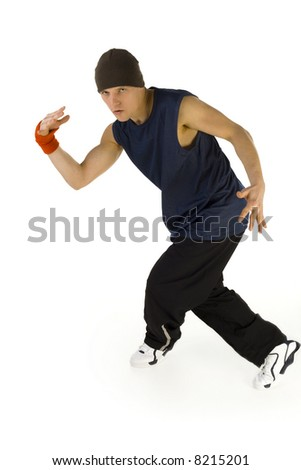 Young man standing in bboy's pose. Looking at camera. Isolated on white in studio. Front view, whole body
