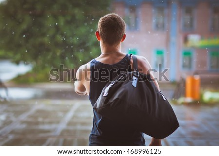 young man standing in the rain on the street in summer