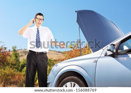 Young man standing near a broken car and talking on a cell phone, on a sunny day - stock photo
