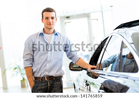 young man standing near a car in a showroom, put his hand on the car door