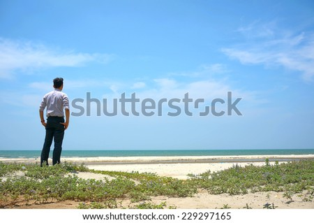 Young man standing near the beach and looking at sea - stock photo