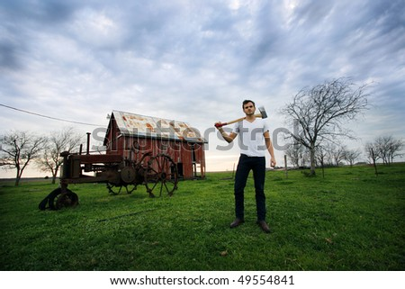 Young man standing next to a barn holding an axe.