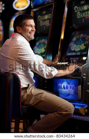 young man standing next to the slot machine smiling