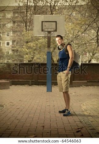 Young man standing on a basketball court - stock photo