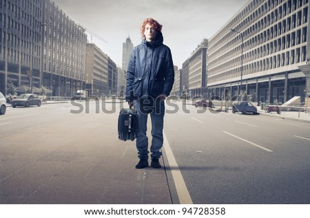 Young man standing on a city street and carrying a trolley case - stock photo