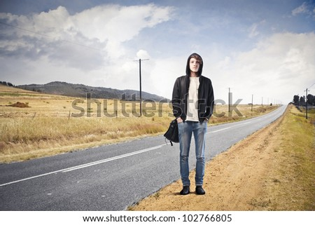 Young man standing on a country road - stock photo