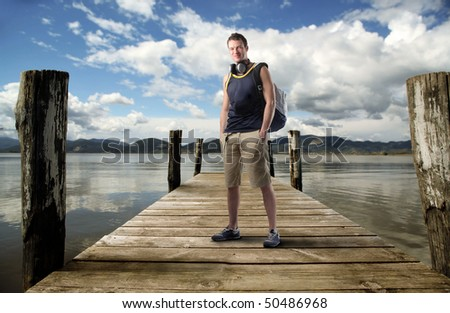 Young man standing on a dock - stock photo