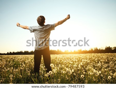 Young man standing on a meadow with dandelions on a blue sky background - stock photo