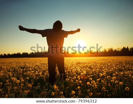 Young man standing on a meadow with dandelions on sunset sky background - stock photo