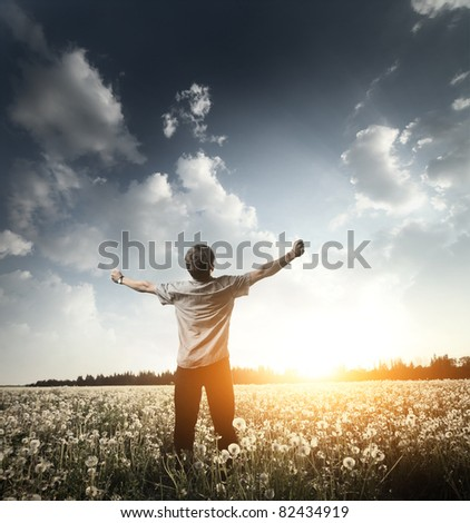 Young man standing on a meadow with raised hands and looking to a sky - stock photo