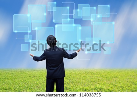 Young man standing on a meadow with raised hands and looking to virtual button
