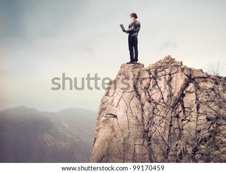 Young man standing on a mountain peak and using a laptop - stock photo