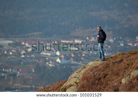 Young man standing on a rock and looking to a valley below - stock photo