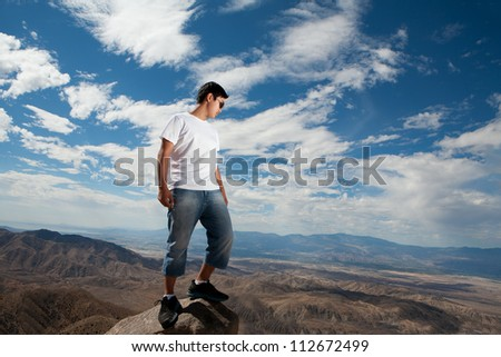 Young man standing on a rock and looking to a valley below