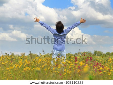Young man standing on a spring meadow with raised hands - stock photo