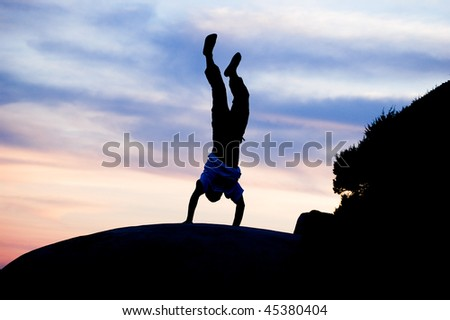 young man standing on arms on the stone on sunset - stock photo