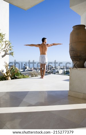Young man standing on balcony, arms outstretched, rear view - stock photo
