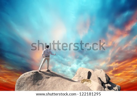 Young man standing on cliff's edge and looking into a wide valley - stock photo