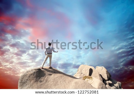 Young man standing on cliff's edge and looking into a wide valley