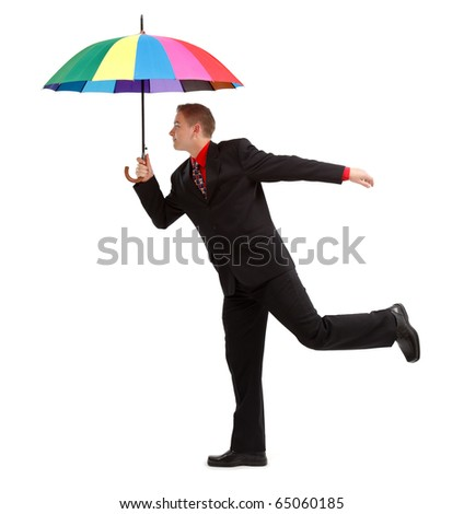 Young man standing on one foot, with big, open, colorful umbrella - stock photo