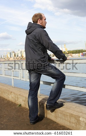 young man standing on river embankment and looking into the distance