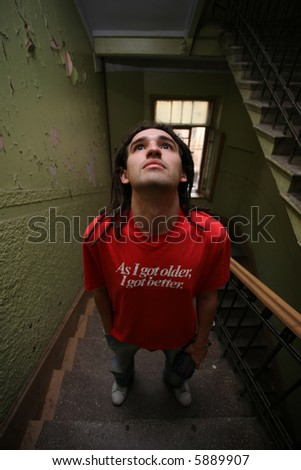 Young man standing on stairway. Wide angle view.