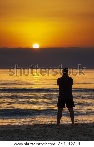 Young man standing on the beach contemplating sunrise or sunset behind wall of clouds - stock photo
