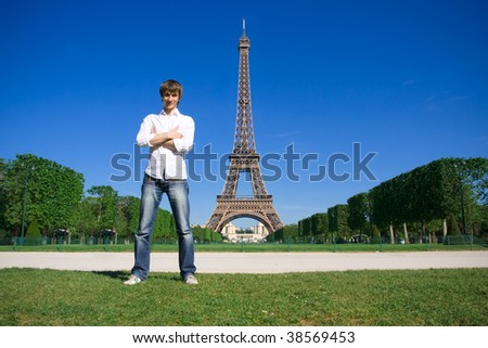 Young man standing on the Champs de Mars. Eiffel tower in background - stock photo