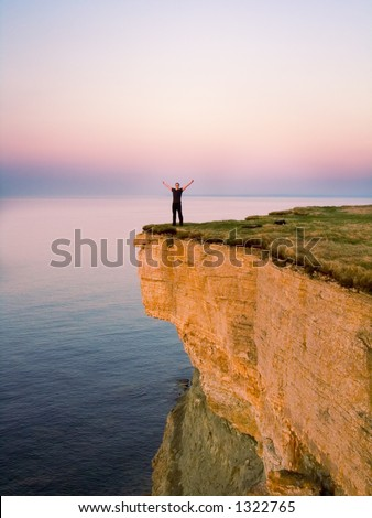 young man standing on the cliff with spreaded hands - stock photo