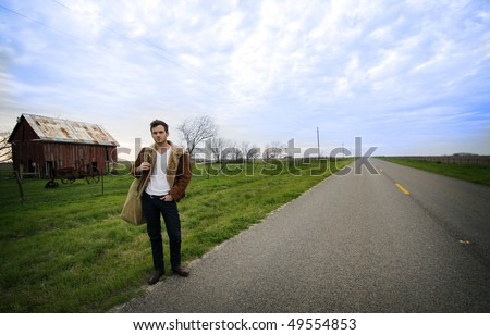 Young man standing on the edge of a country road.