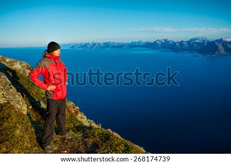 Young man standing on the top of mountain Festvagtinden with picturesque scenery of Lofoten islands, Norway - stock photo