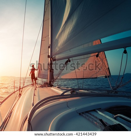 Young man standing on the yacht in the sea at sunset