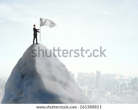 young man standing on top of mountain with flag - stock photo