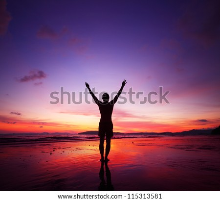 Young man standing on tropical beach with raised hands at sunset - stock photo