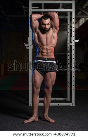 Young Man Standing Strong In The Gym And Flexing Muscles - Muscular Athletic Bodybuilder Fitness Model Posing Showing Abs After Exercises - stock photo