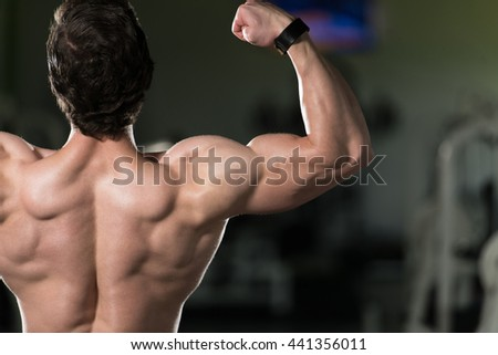 Young Man Standing Strong In The Gym And Flexing Rear Double Biceps Pose - Muscular Athletic Bodybuilder Fitness Model Posing Exercises - stock photo
