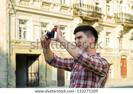 Young man standing taking photographs with a compact camera outside an old historical building - stock photo