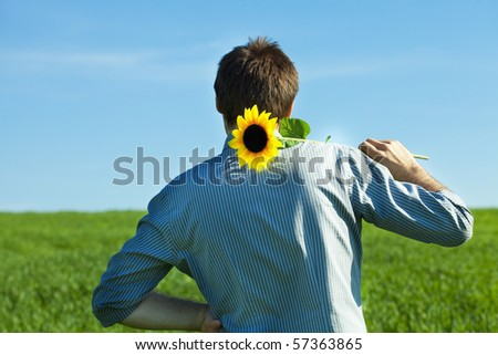 young man standing with a sunflower in the green field - stock photo