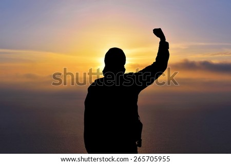 Young man standing with arms outstretched at sunset - stock photo