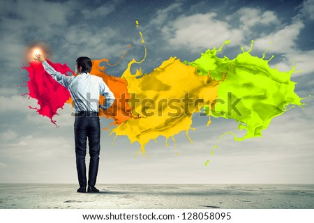young man standing with back painting splashes with fingers - stock photo