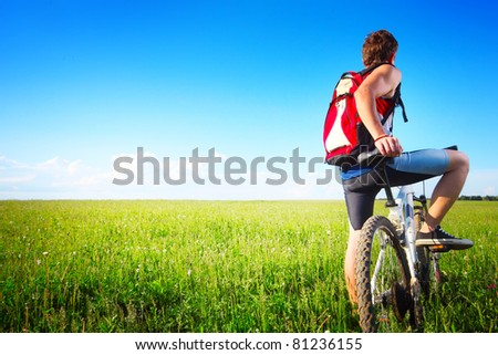 Young man standing with bicycle on a green grass and looking to the horizon - stock photo