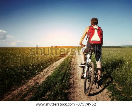 Young man standing with bicycle on an countryside road - stock photo